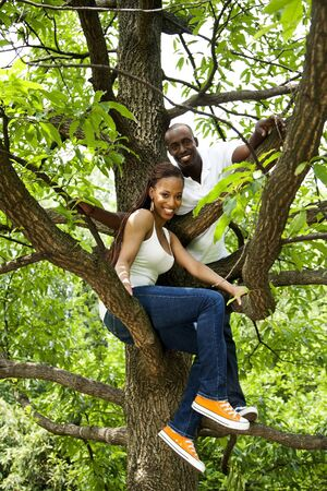 Beautiful happy fun smiling African American couple in tree, wearing white shirts and blue jeans. photo