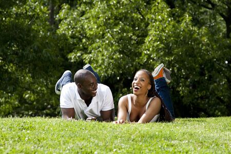 Beautiful fun happy smiling laughing African American couple joking laying on grass in park, wearing white shirts and blue jeans. photo