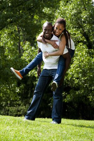 Beautiful fun happy smiling laughing African American couple piggyback playing in the park, woman hugging man, wearing white shirts and blue jeans.