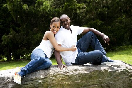 Beautiful fun happy smiling African American couple in love wearing white shirts and blue jeans, sitting on a rock in a park, woman hugging guy.
