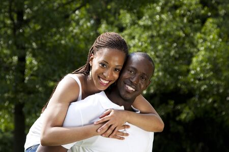 Beautiful happy smiling young African American couple in love wearing white shirts, woman hugging man, with trees in the background. photo