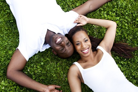 girl lying: Beautiful fun happy smiling African American couple wearing white shirts laying in grass, faces of woman and man next to eachother in opposite direction.