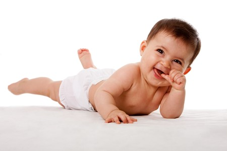 laughing baby: Happy cute baby laying with thumb in mouth, isolated.