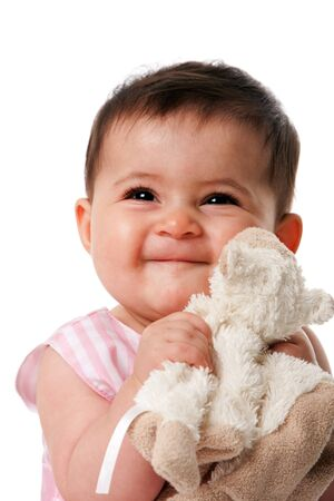 Beautiful happy cute baby girl smiling face with security blanket toy, isolated. Imagens