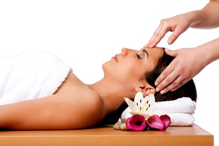 facial: Beautiful happy peaceful sleeping woman at a spa, laying on wooden massage table with head on pillow wearing a towel getting a facial massage, isolated.