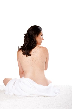 Beautiful woman sitting nude on soft surface with a towel around her bottom showing bare back with freckles, isolated.