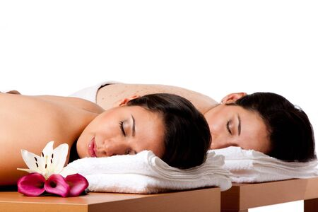 Two beautiful women friends laying on wooden tables with head on towels waiting for their massage in the spa, isolated. photo