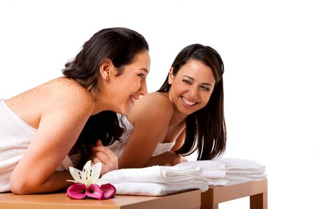 Two beautiful women friends laying on wooden tables with towels waiting for their massage in the spa, smiling laughing talking and having fun, isolated. photo