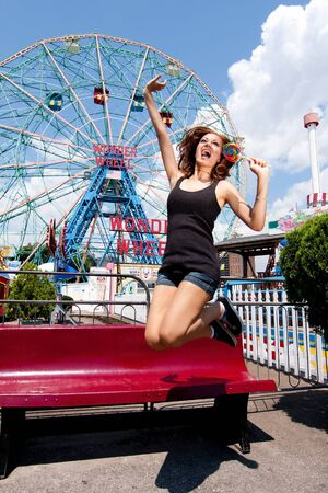 coney: Beautiful fun happy girl jumping and eating colorful lollipop at the Wonder Wheel in Coney Island carnival amusement theme park.