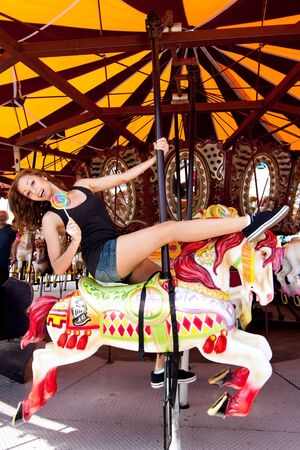 Beautiful fun happy girl riding horse in carousel merry go round in Coney Island carnival amusement theme park. 免版税图像