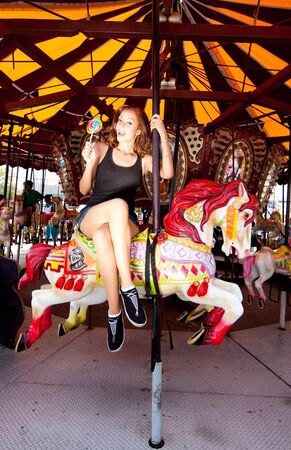 Beautiful fun happy smiling girl riding horse in carousel merry go round in Coney Island carnival amusement theme park. 免版税图像