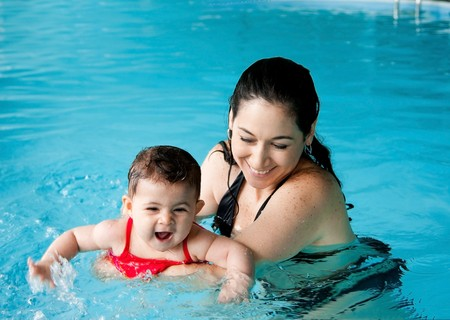 Beautiful mother teaching cute baby girl how to swim in a swimming pool. Child having fun in water with mom. photo