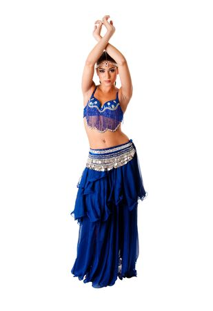 belly dancing: Beautiful Arabic belly dancer harem woman in blue with silver dress and head jewelry with gem dancing arms in air, isolated.