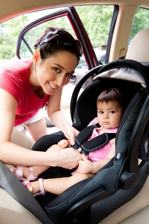 buckle: Happy smiling mother placing baby in car seat and closing belt for safety.
