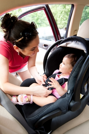 Happy smiling mother placing baby in car seat and closing belt for safety. photo