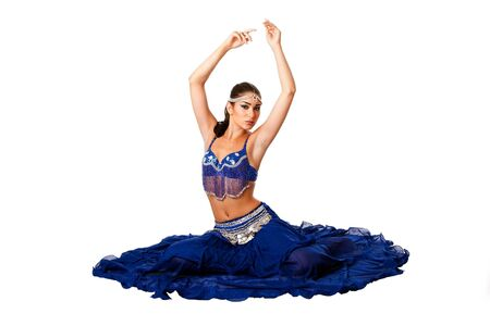 Beautiful Israeli Egyptian Lebanese Middle Eastern belly dancer performer in blue skirt and bra with arms in air sitting, isolated.