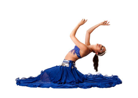 belly dancer: Beautiful Israeli Egyptian Lebanese Middle Eastern belly dancer performer in blue skirt and bra with arms in air sitting and bending backwards, isolated.