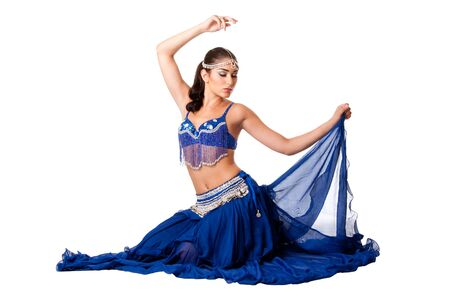 Beautiful Israeli Egyptian Lebanese Middle Eastern belly dancer performer in blue skirt and bra with arm in air sitting with eyes closed, isolated.