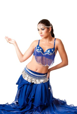 israeli: Beautiful Israeli Egyptian Lebanese Middle Eastern fashion belly dancer performer in blue skirt and bra sitting on knees, isolated. Stock Photo