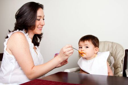 Beautiful happy mother or nanny feeds baby boy girl orange puree with spoon, infant eats messy, while sitting at table.
