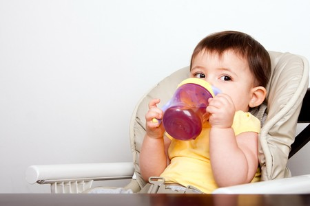 Cute baby infant boy girl sitting in chair drinking from sippy cup.