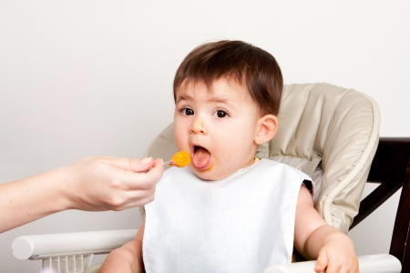 Beautiful happy baby infant boy girl with mouth open eating messy orange puree from spoon.