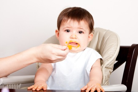 dislike: Cute baby infant boy girl expresses dislike disgust for food fed by spoon. Stock Photo