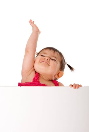 Cute beautiful happy baby infant girl holding white board while reaching up in the air with pride, isolated. Stock Photo