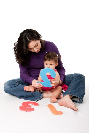 Mother, nanny, or teacher teaching baby to learn how to count one, two, three, with numbers in a playful way, while sitting on floor.