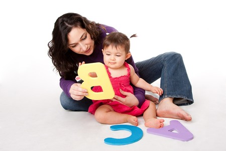 Mother, nanny, or teacher teaching happy baby to learn alphabet, A, B, C, with letters in a playful way, while sitting on floor.