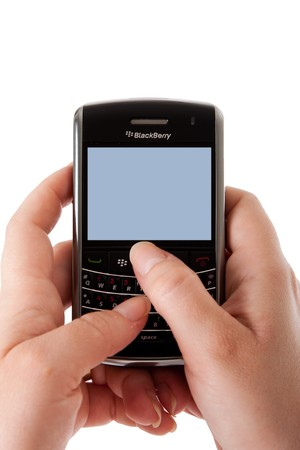 Woman hands using a Blackberry Bold smartphone computer with blank screen for apps, optical trackpad and keyboard, sim card, isolated.