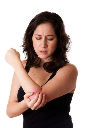 elleboog: Mooie vrouw houdt van haar elleboog met pijn en arm pijn, het dragen van een sportieve zwarte tank top, geïsoleerd.  Stockfoto