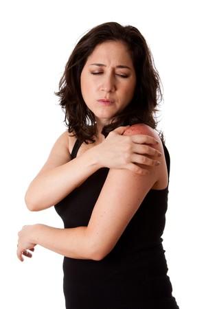 douleur epaule: Femme belle tenant son �paule avec douleur et mal, portant un sportif noir d�bardeur, isol�.  Banque d'images