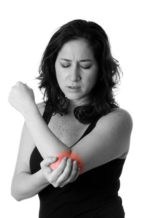 elbows: Beautiful woman holding her elbow with pain and arm ache,wearing a sporty black tank top, isolated. Stock Photo