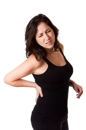 hernia: Beautiful woman holding her back with pain and ache due to injury,wearing a sporty black tank top, isolated. Stock Photo