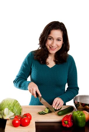 Beautiful woman cutting cucumber in kitchen, cooking and preparing to make a salad, isolated. photo