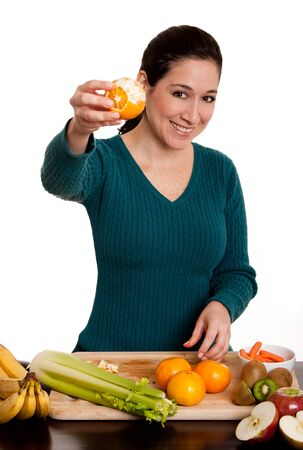 Happy beautiful woman presenting a delicious organic peeled orange fruit full with vitamin C in kitchen, isolated.