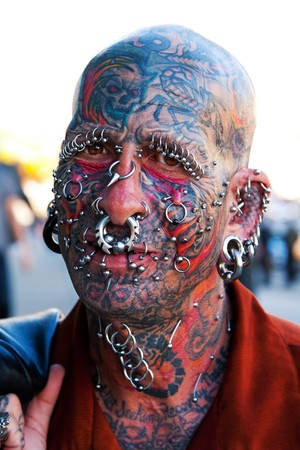 Portrait of famous Dennis Lang with his face full of tattoos and piercings.