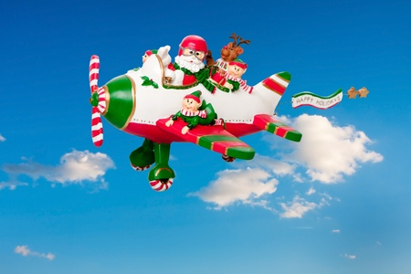 elves: Santa Claus flying his airplane with Happy Holidays banner in the sky with his elves and Rudolf the Red nosed Reindeer. Stock Photo