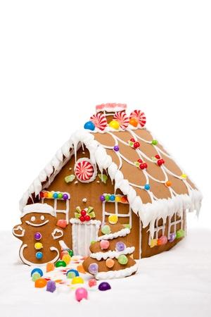 case colorate: La casa di marzapane, uomo e albero di Natale ricoperte di neve e caramelle colorate su un paesaggio invernale, isolato.