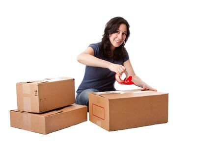 Attractive happy beautiful woman putting tape on cardboard moving storage boxes parcels preparing for mail, isolated. Zdjęcie Seryjne