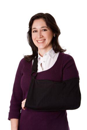 Gelukkig aantrekkelijke vrouw met gebroken arm in sling, geïsoleerd. Stockfoto
