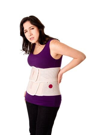 Woman in pain from back injury wearing an orthopedic body brace corset, isolated.