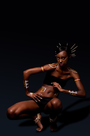 tribal dance: Beautiful exotic African female fashion with tribal yellow red and white makeup cosmetics and sticks in hai, in dance position.