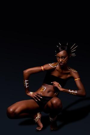 danza africana: Bella esotica femmina moda africana con cosmetici trucco giallo tribale di rosso e bianco e bastoni a hai, in posizione di danza.