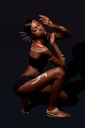 Beautiful exotic African female fashion with tribal yellow red and white makeup cosmetics and sticks in hair, in cultural dance position. Stock Photo