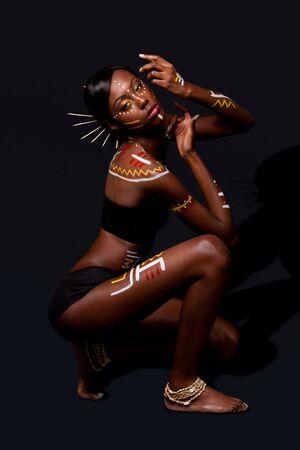 Hermosa exótica mujer Moda Africana con palos en pelo, en posición de danza cultural y cosméticos tribales maquillaje amarillo de rojo y blanco.