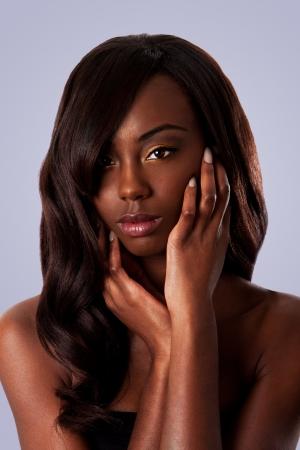 cabello negro: Hermoso rostro de una mujer negra africana atractiva con almendra en forma de ojos y cabello largo ondulado y manos en su rostro, aislado.