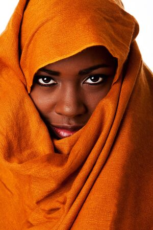 Beautiful mysterious african nomadic female face in ocher Earth tone head wrap scarf looking.