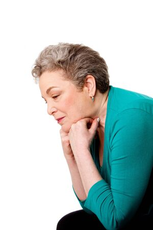 thinking woman: Beautiful Senior woman worried leaning forward on her hands thinking of her future or past life, isolated.